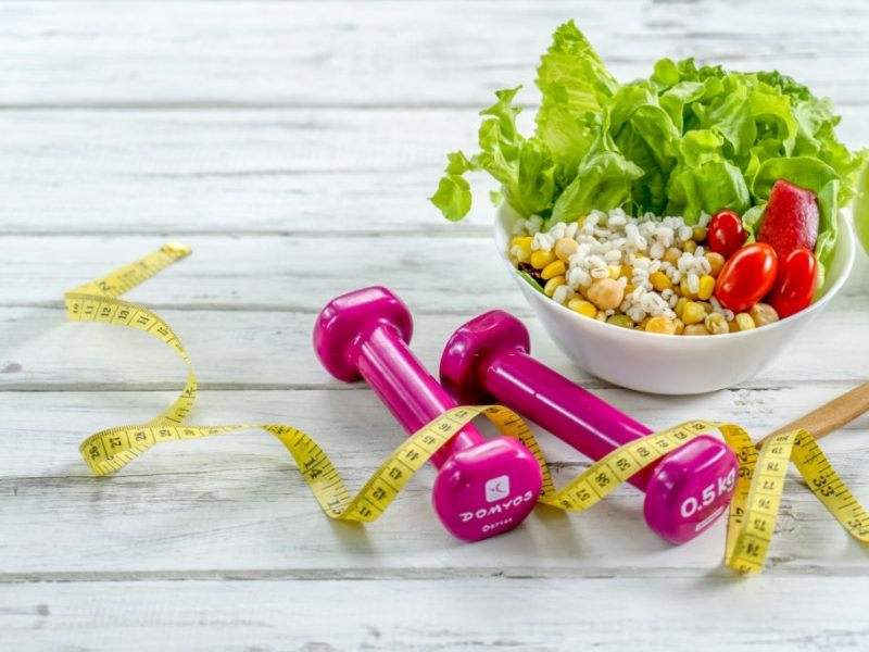 Workout and fitness dieting copy space diary. Healthy lifestyle concept. Dumbbell, vegetable salad and measuring tape on rustic wooden table.